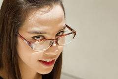 Beautiful woman look through her eyeglasses on plain background Stock Photos
