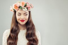 Beautiful woman looking aside. Indoor portrait of perfect female model in summer flowers wreath over gray background. Use copy. Space wisely stock photos