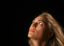 Beautiful Woman Looking Away. Beautiful Blond Woman Looking Up and Away on Black Background stock photos