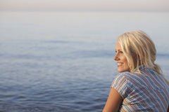 Beautiful Woman Looking Away While Sitting At Beach Stock Photo