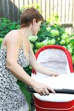 Beautiful woman looking in baby stroller Stock Photo