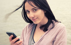 Beautiful woman looking at camera in european city using her smartphone water of river on background Royalty Free Stock Image