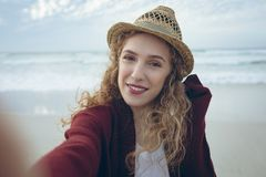 Beautiful woman looking at camera standing at beach. Portrait of beautiful young Caucasian woman with hat looking and smiling at camera standing at beach stock image