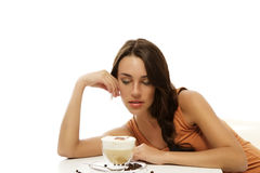 Beautiful woman looking at the cappuccino coffee i Stock Image