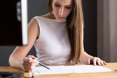 Beautiful woman looking at contract at the desk Stock Photography