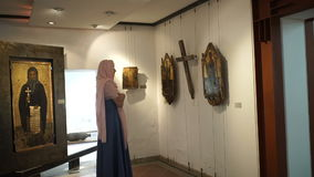 Beautiful woman looking on the exhibits in religious museum. Beautiful woman in pink headscarf and long blue dress staying in the museum. She`s looking on the stock footage