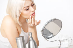 Beautiful Woman Looking at Her Face in the Miror Doing Daily Morning Makeup Stock Images