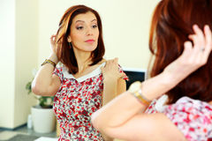 Beautiful woman looking on her reflection in the mirror Stock Photography