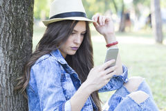 Beautiful woman looking on her smart phone outdoors Royalty Free Stock Image