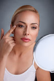 Beautiful woman looking her wrinkles in mirror. Beauty in middle age royalty free stock images