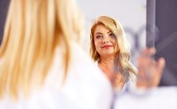 Beautiful woman looking at herself in the mirror in the bathroo. M stock images