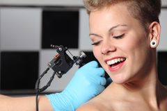 Beautiful woman looking how somebody is making a tattoo. On her shoulder Royalty Free Stock Photo