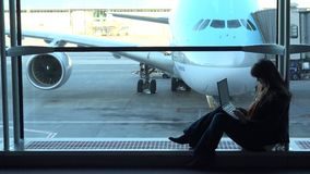 Beautiful woman looking at laptop in airport, sitting at big window, airplane parked. UHD 4K stock footage