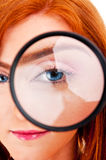Beautiful woman looking through a magnifying glass Royalty Free Stock Image