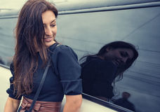 Beautiful woman looking at the man in the reflection of automotive glass. Royalty Free Stock Image