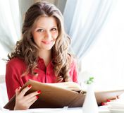 Beautiful woman looking at menu and ordering foods in cafe Royalty Free Stock Image