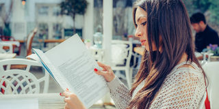 Beautiful woman looking at menu and ordering foods in restaurant Stock Photos