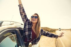 Happy girl looking out the car window stock photography