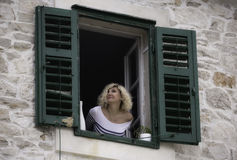 Beautiful woman is looking out the window, leaning on the windowsill Royalty Free Stock Image