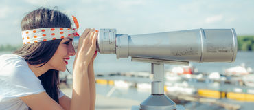 Beautiful woman looking over city through tourist telescope, Bel Royalty Free Stock Image