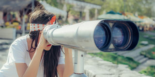 Beautiful woman looking over city through tourist telescope, Bel Royalty Free Stock Photography