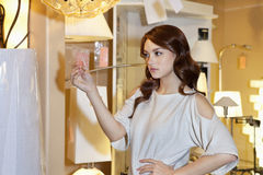 Beautiful woman looking at price tag of lighting fixture with hand on hip while standing in lights store Royalty Free Stock Photos