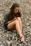 Beautiful woman looking sad. Beautiful brunette woman holding her legs and looking sad Stock Image