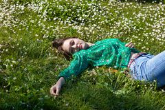 Beautiful woman looking  sensual in camera lying down in  a meadow royalty free stock photos