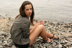 Beautiful woman looking serious. Thoughtful young girl sit on the river bank Stock Photos