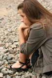 Beautiful woman looking serious. Thoughtful young girl sit on the river bank and looking frontwards Stock Image