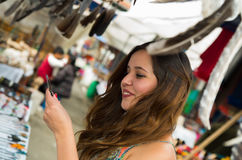 Beautiful woman looking something in the andean traditional clothing and handicrafts with a blurred feather in front. Market background Stock Photo