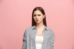 Beautiful woman looking suprised and bewildered isolated on pink. Why is that. Beautiful female half-length portrait isolated on trendy pink studio backgroud Royalty Free Stock Image