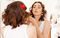 Woman looking to the mirror Stock Photos