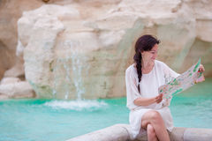 Beautiful woman looking at touristic citymap near Trevi Fountain, Rome, Italy. Happy girl enjoy italian vacation holiday Stock Photos