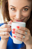 Beautiful woman looking up and drinking a cup of coffee Royalty Free Stock Photography