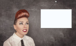 Beautiful woman looking up on empty banner. On the blackboard background Royalty Free Stock Images