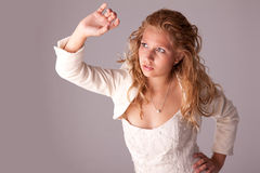 Beautiful woman, looking up protection. With the arm from the light, studio shot Royalty Free Stock Photos