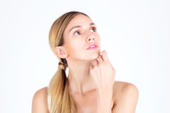 Beautiful woman looking up and touching face with her hands Stock Photos