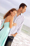 Beautiful woman looking at viewer and handsome man. A tall young handsome man is looking out towards the ocean while his beautiful woman holds him and looks at Royalty Free Stock Photos