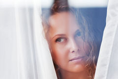 Beautiful woman looking through a window. Portrait of beautiful woman looking through a window Royalty Free Stock Image