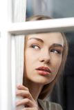 Beautiful woman is looking through window. Indoor background Stock Images