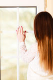 Beautiful woman looking through window. Stock Photography