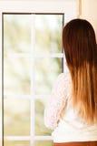 Beautiful woman looking through window. Stock Image