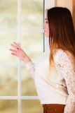 Beautiful woman looking through window. Royalty Free Stock Photos