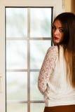 Beautiful woman looking through window. Royalty Free Stock Photos