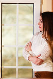 Beautiful woman looking through window. Stock Images