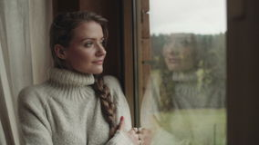 Beautiful woman looking through a window and smiling. stock video
