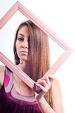 Beautiful woman looking through wooden frame Stock Photography