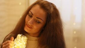 Beautiful woman looks at the lights, closes her eyes, makes a wish and dreams. Background with bokeh lights. Closeup portrait stock video