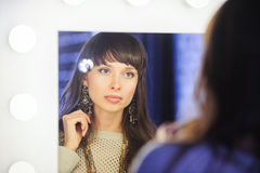 Beautiful woman looks in the mirror royalty free stock image